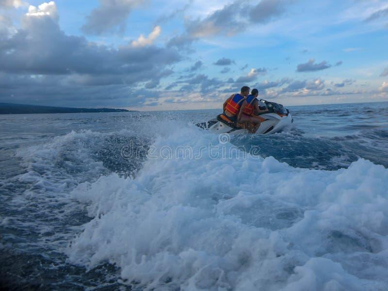 漂移横跨海表面的年轻人和妇女 喷气机滑雪的人们获得乐趣在海洋 在行动的司机在飞溅水期间 免版税库存照片