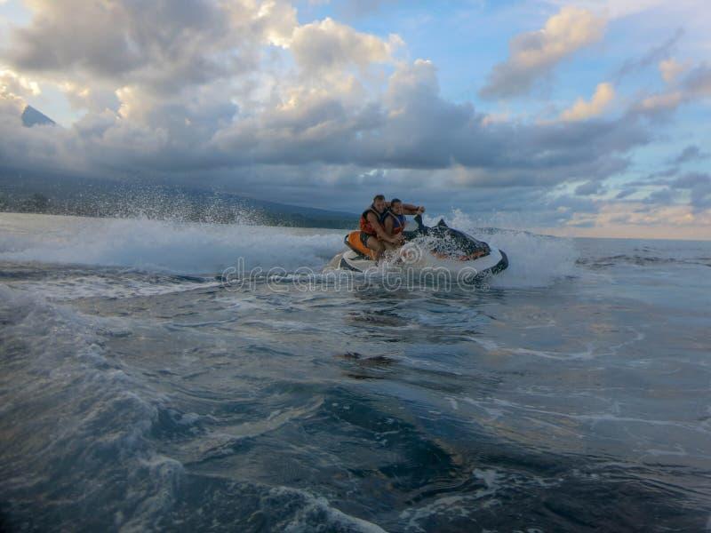 漂移横跨海表面的年轻人和妇女 喷气机滑雪的人们获得乐趣在海洋 在行动的司机在飞溅水期间 图库摄影