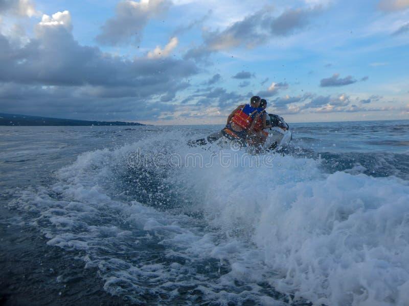 漂移横跨海表面的年轻人和妇女 喷气机滑雪的人们获得乐趣在海洋 在行动的司机在飞溅水期间 库存照片