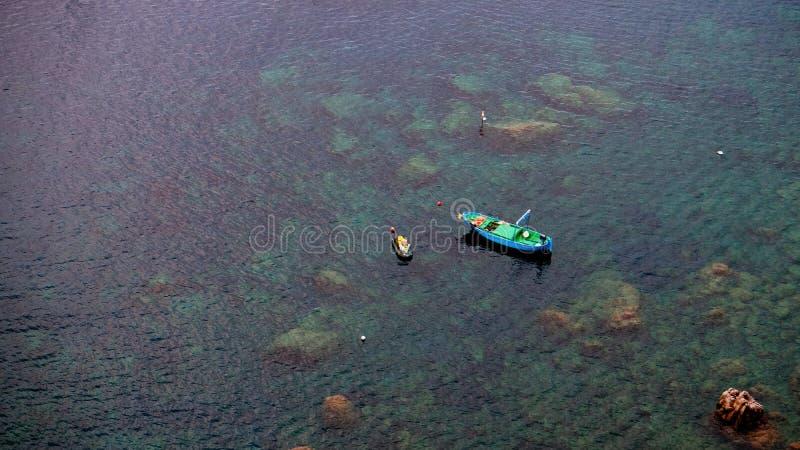 漂移由在透明水的意大利岸的孤立蓝色小船 免版税库存照片