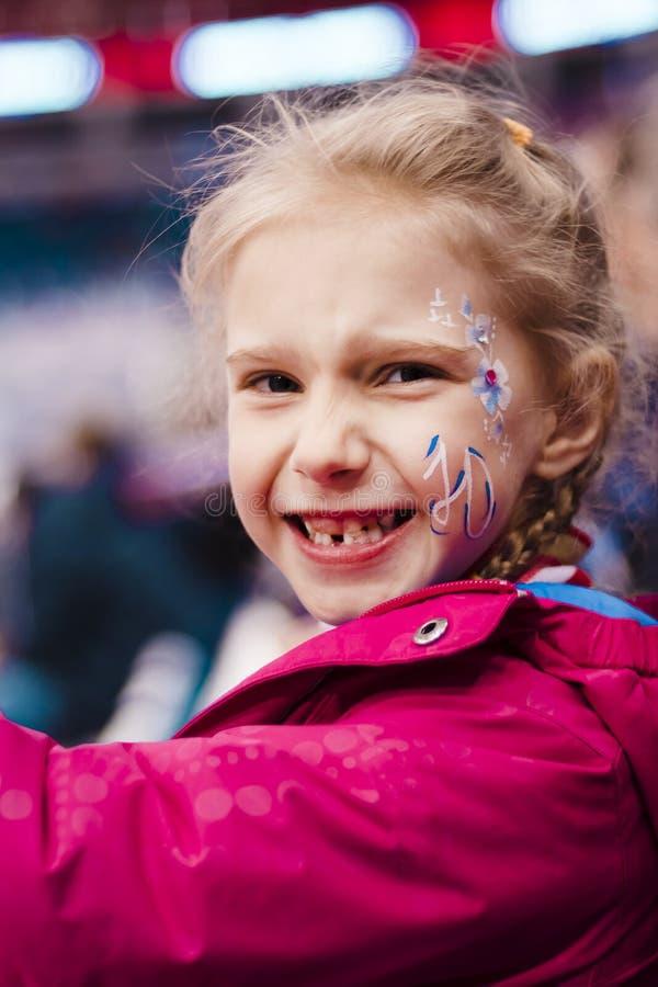 演出的照片 指挥台的女孩金发碧眼的女人 有在面颊的题字 她是高兴的队赢得 ? 免版税库存照片