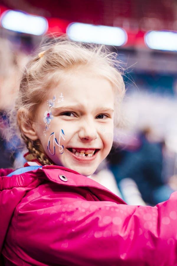 演出的照片 指挥台的女孩金发碧眼的女人 有在面颊的题字 她是高兴的队赢得 ? 库存图片