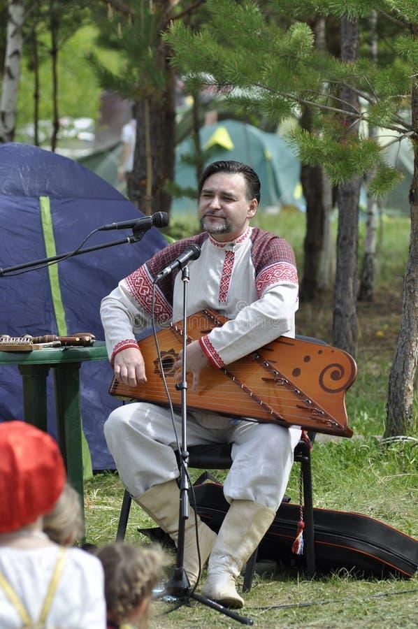 演员音乐家在古代弦乐器使用在天空和地球ethn 免版税库存图片