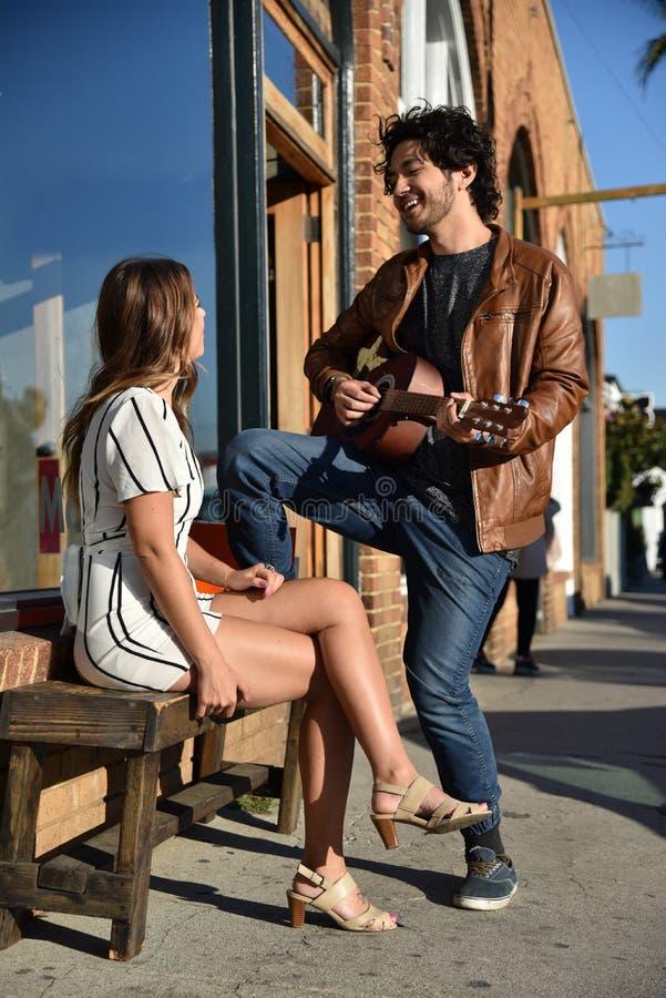 演唱女孩的愉快的年轻人 免版税库存图片