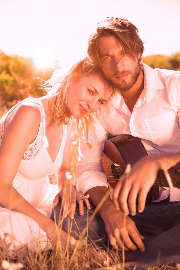 演唱他的有吉他的英俊的人女朋友微笑对照相机 皇族释放例证
