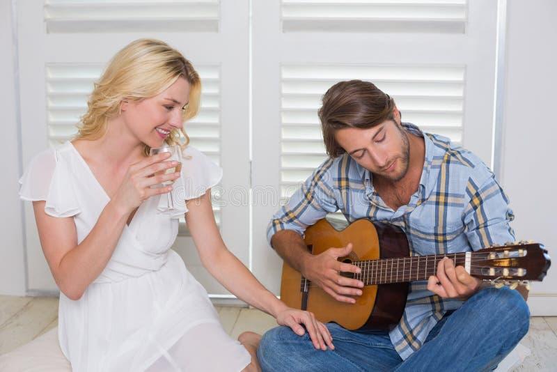 演唱他的有吉他的英俊的人女朋友 图库摄影