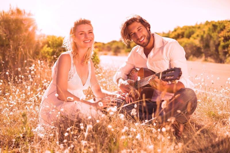 演唱他的有吉他的英俊的人女朋友 库存例证