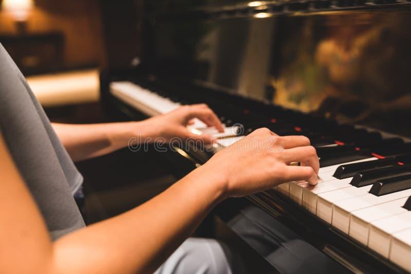 演奏一架钢琴的键盘的在浪漫大气的亚洲妇女手 乐器,独奏钢琴演奏家,歌曲作曲家概念 免版税库存照片