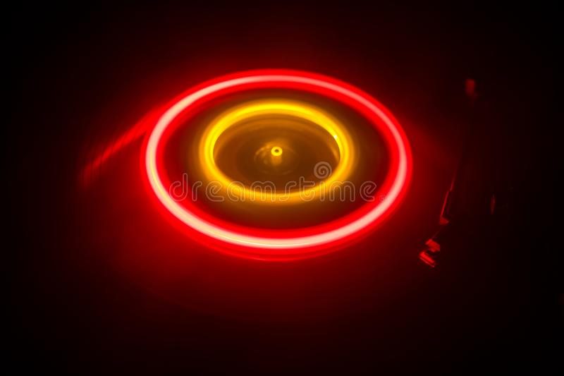 演奏与发光的抽象线概念的转盘乙烯基在黑暗的背景 库存照片