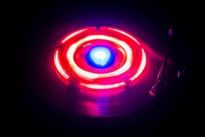 演奏与发光的抽象线概念的转盘乙烯基在黑暗的背景 图库摄影
