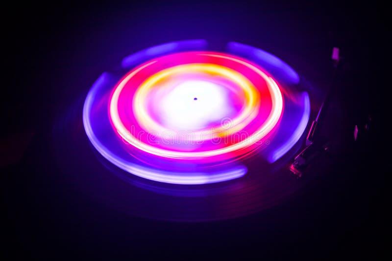 演奏与发光的抽象线概念的转盘乙烯基在黑暗的背景 免版税图库摄影
