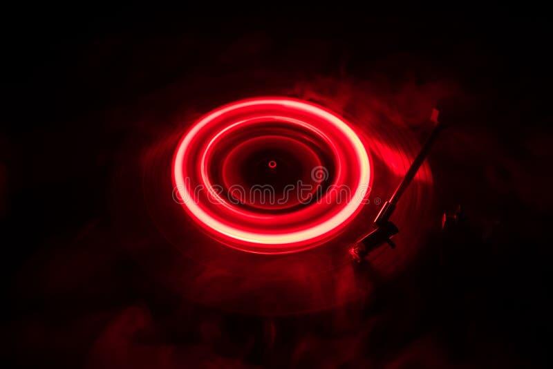 演奏与发光的抽象线概念的转盘乙烯基在黑暗的背景 免版税库存照片