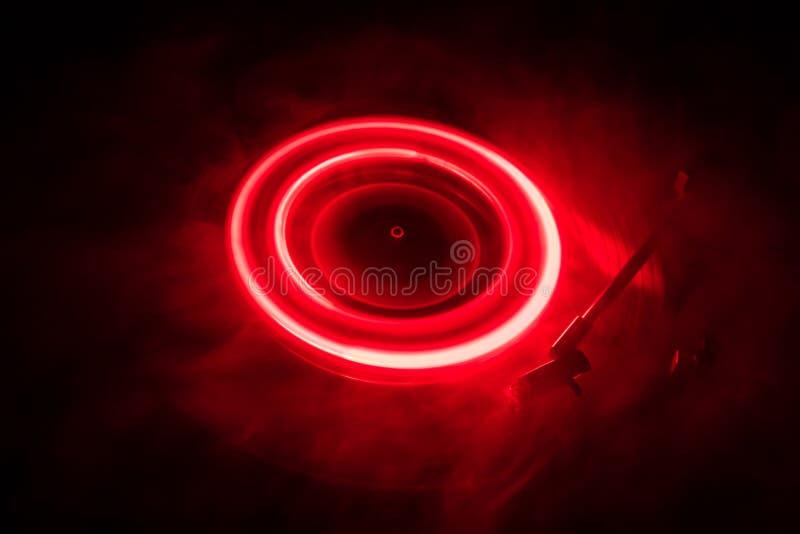 演奏与发光的抽象线概念的转盘乙烯基在黑暗的背景 库存图片
