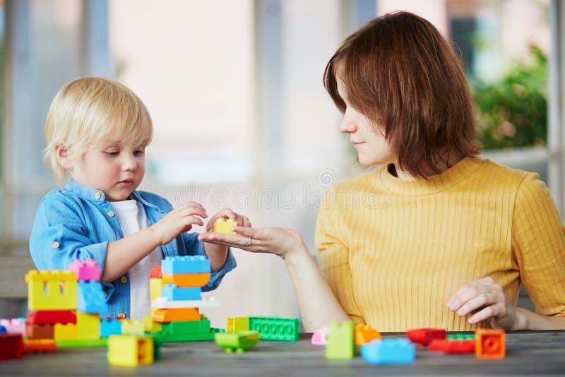演奏与她的儿子的母亲五颜六色的建筑块 库存图片