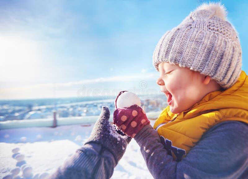 演奏与家庭的愉快的小孩男婴雪球晴朗的冬日 免版税库存图片