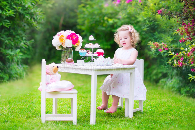 演奏与玩偶的卷曲甜小孩女孩茶会 免版税图库摄影
