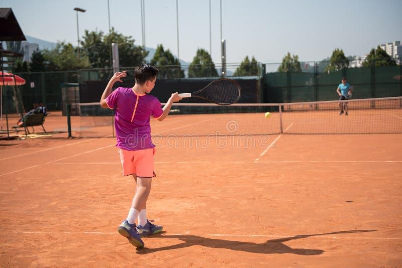 演奏与hgh冲击的年轻网球员正手击球 免版税图库摄影