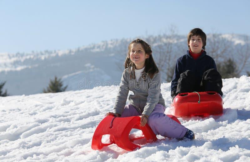 演奏与sledon在山的寒假雪 免版税库存图片