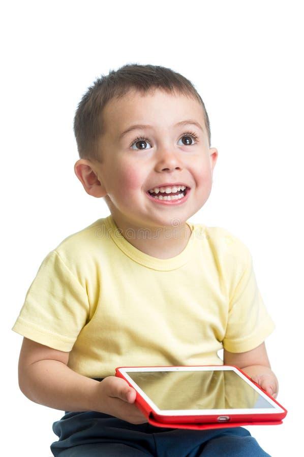 演奏个人计算机片剂的微笑的孩子 图库摄影