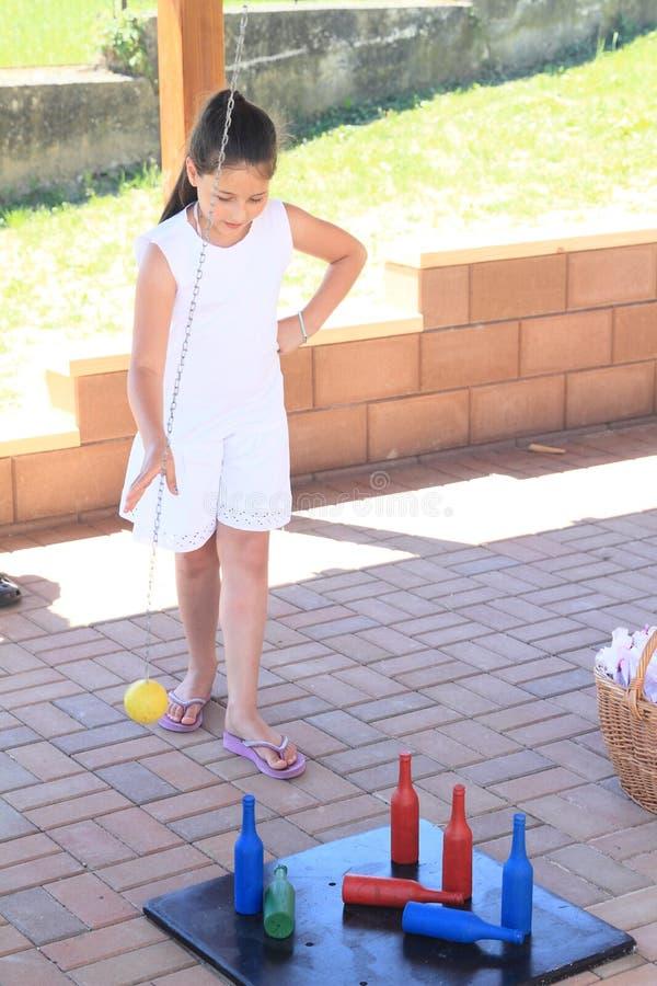 演奏九柱游戏用的小柱的白色的女孩 库存照片