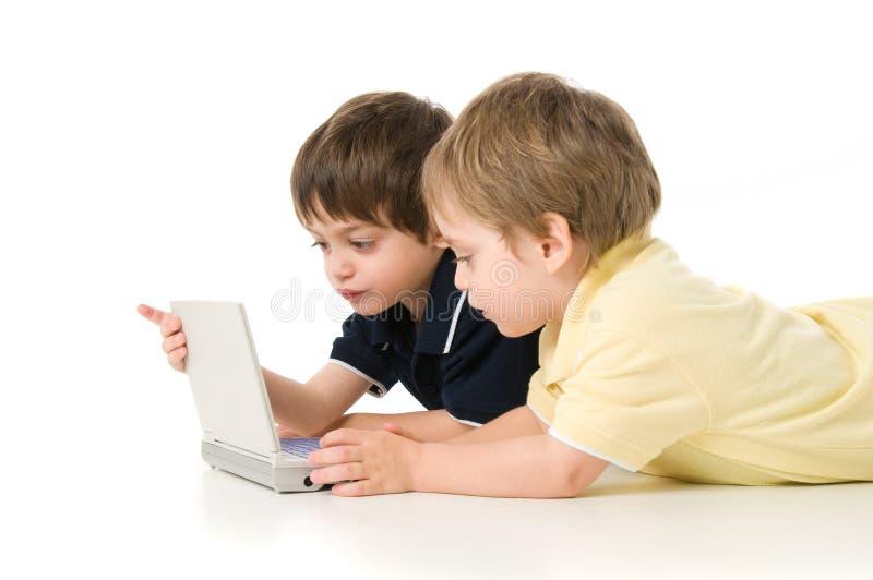 演奏二的儿童膝上型计算机 免版税库存图片