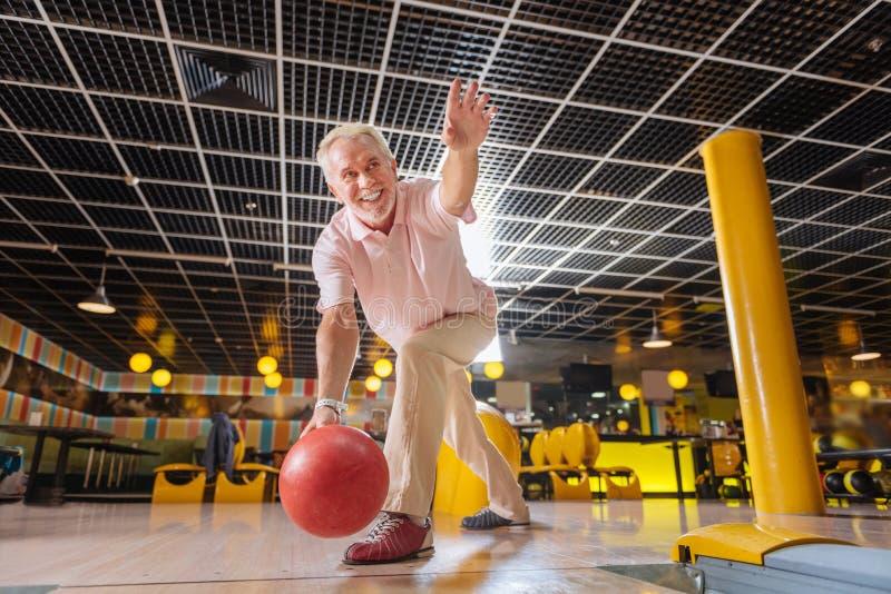 演奏保龄球和微笑的快乐的好年迈的人 免版税库存照片