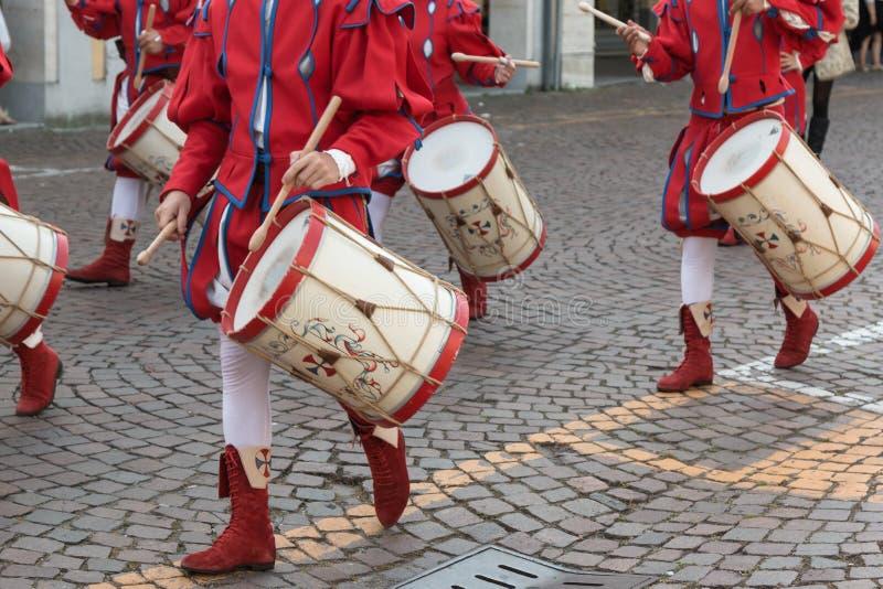 演奏军鼓的红色和白色制服的鼓手 免版税库存图片