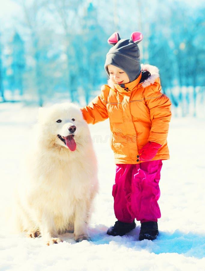 演奏冬天的孩子和白色萨莫耶特人狗给爪子 库存照片