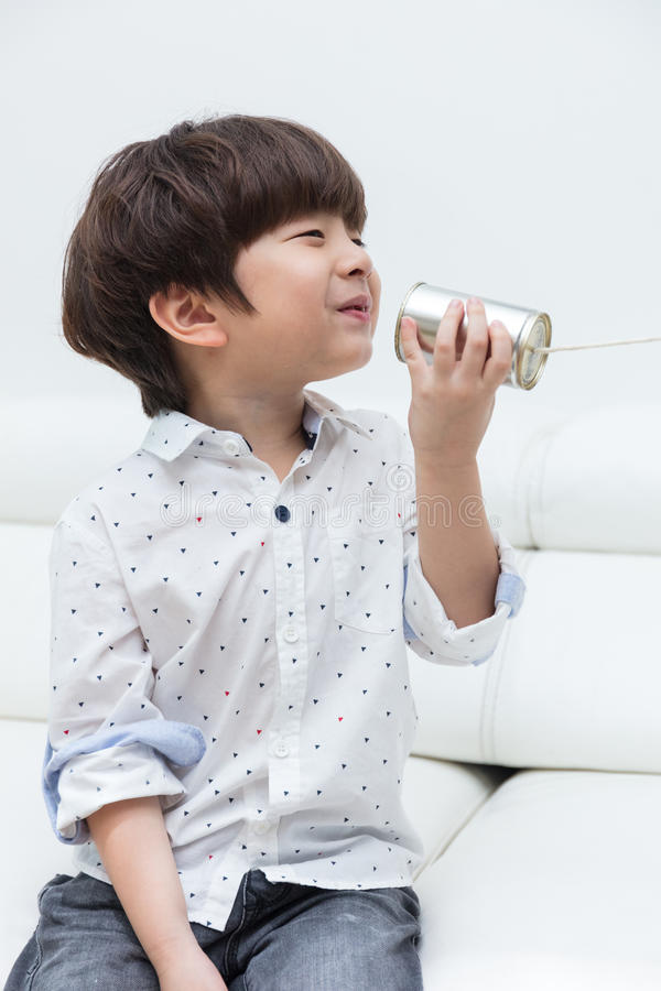 演奏减速火箭的锡罐电话的亚裔中国小男孩 图库摄影