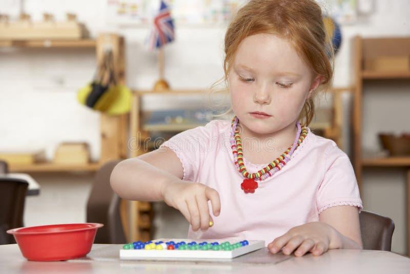演奏前学校年轻人的女孩montessori 库存图片