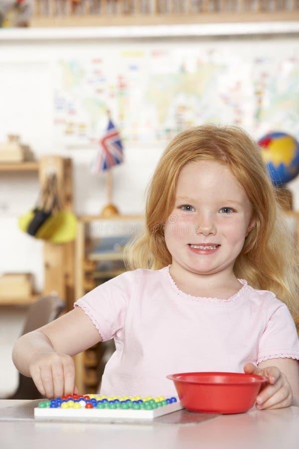 演奏前学校年轻人的女孩montessori 库存照片