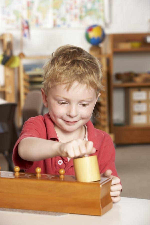 演奏前学校年轻人的男孩montessori 库存照片