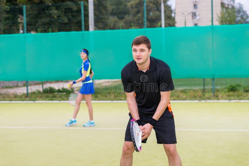 演奏双的两个年轻网球员户外 免版税库存照片