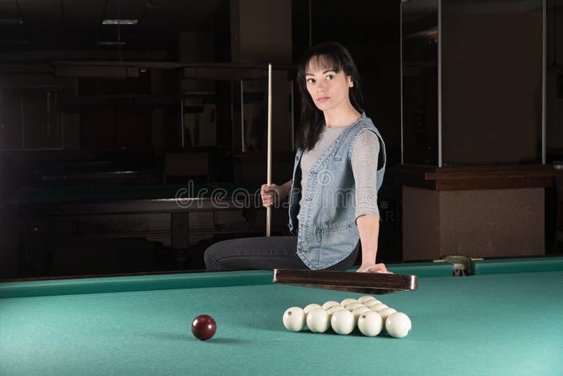演奏台球的女孩 拿着球杆的妇女 免版税图库摄影