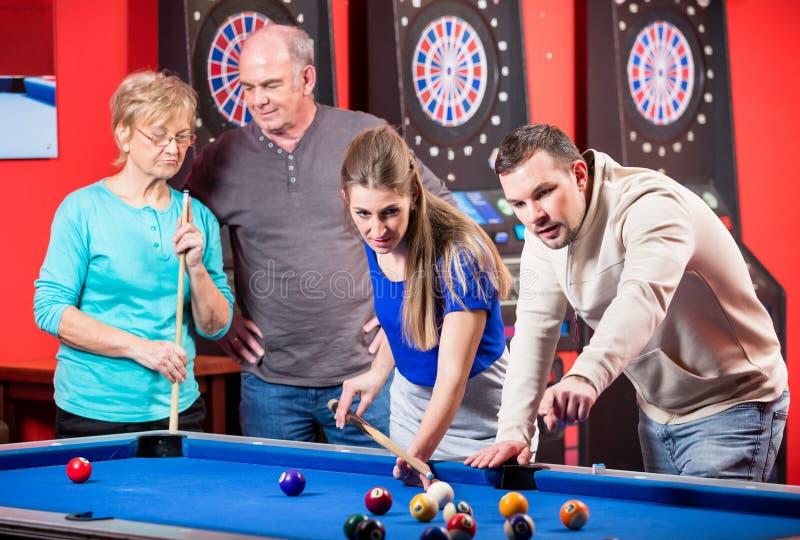 演奏台球的年轻和成熟夫妇 免版税库存照片