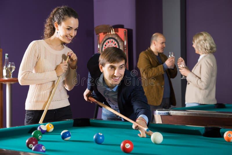 演奏台球的年轻夫妇 库存照片