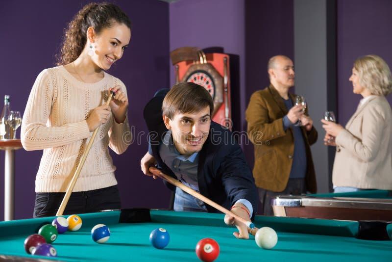 演奏台球的年轻美好的夫妇 库存照片