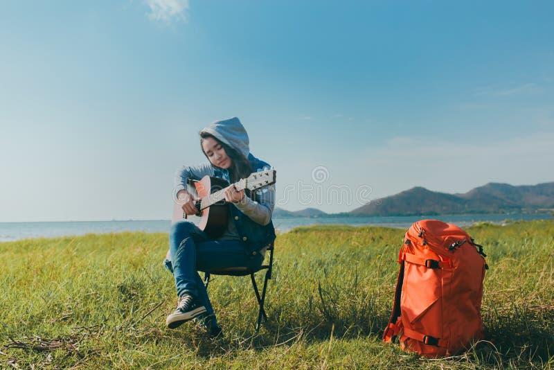 演奏吉他休息的亚裔妇女少年室外在迁徙与背包 免版税库存照片
