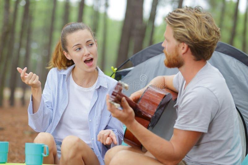 演奏吉他伙伴的男朋友唱歌在帐篷之外 图库摄影