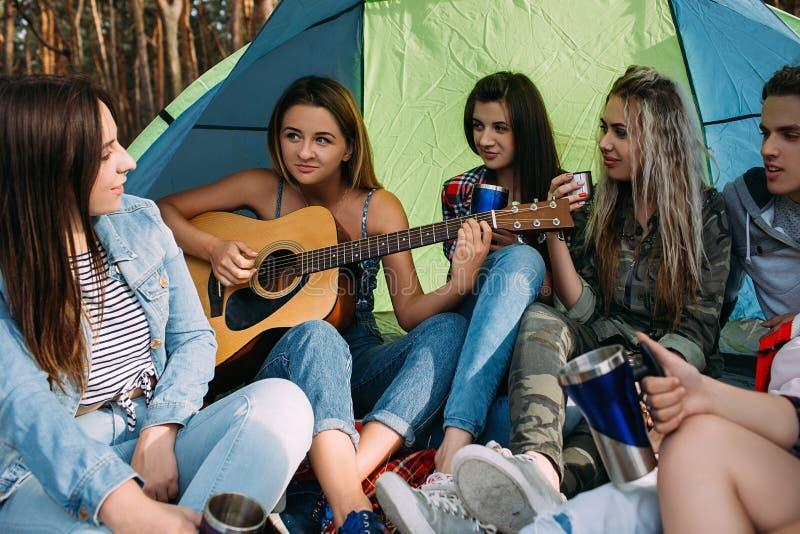 演奏吉他帐篷森林朋友概念的俏丽的女孩 免版税图库摄影