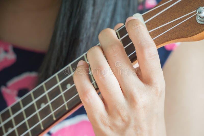演奏吉他或尤克里里琴弦的手 免版税库存照片