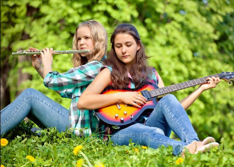 演奏吉他和长笛的两个女孩在公园 免版税库存照片