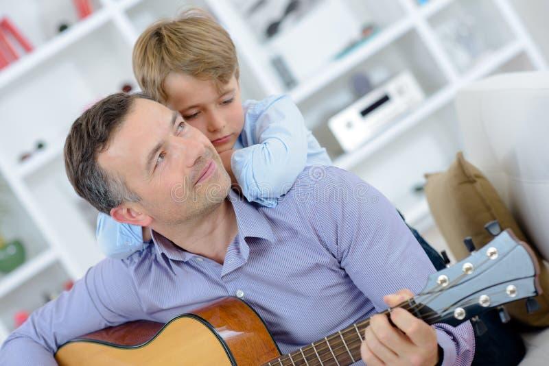 演奏吉他男孩的人倾斜在肩膀 库存图片