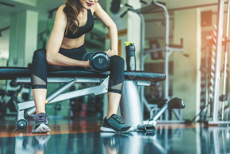 演奏哑铃在健身g的亚裔少妇锻炼锻炼 免版税库存照片