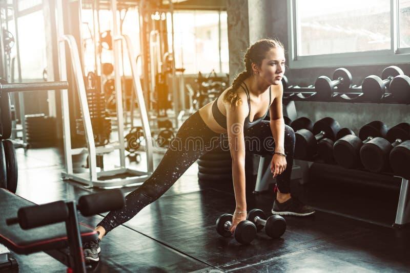 演奏哑铃的女孩对在健身的锻炼 亭亭玉立的女孩lif 免版税图库摄影
