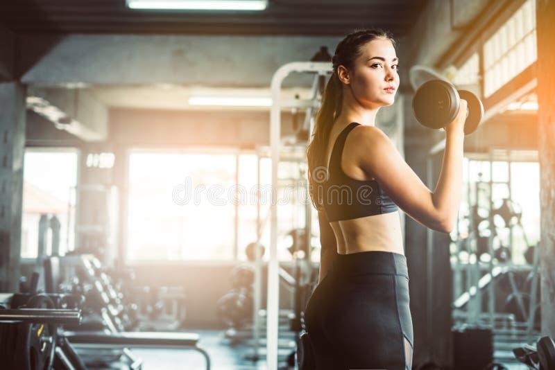 演奏哑铃的女孩对在健身的锻炼 亭亭玉立的女孩lif 库存照片