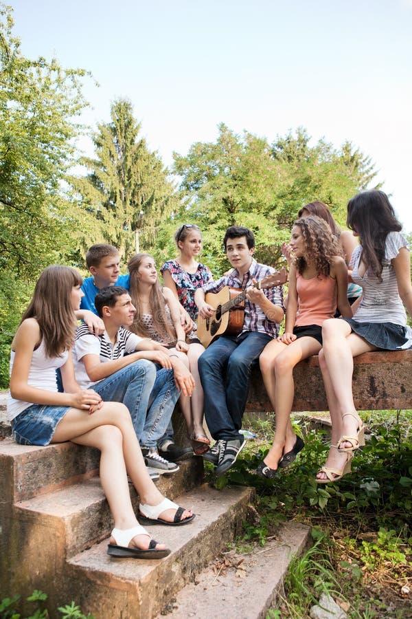演奏唱歌的少年的吉他 免版税库存图片