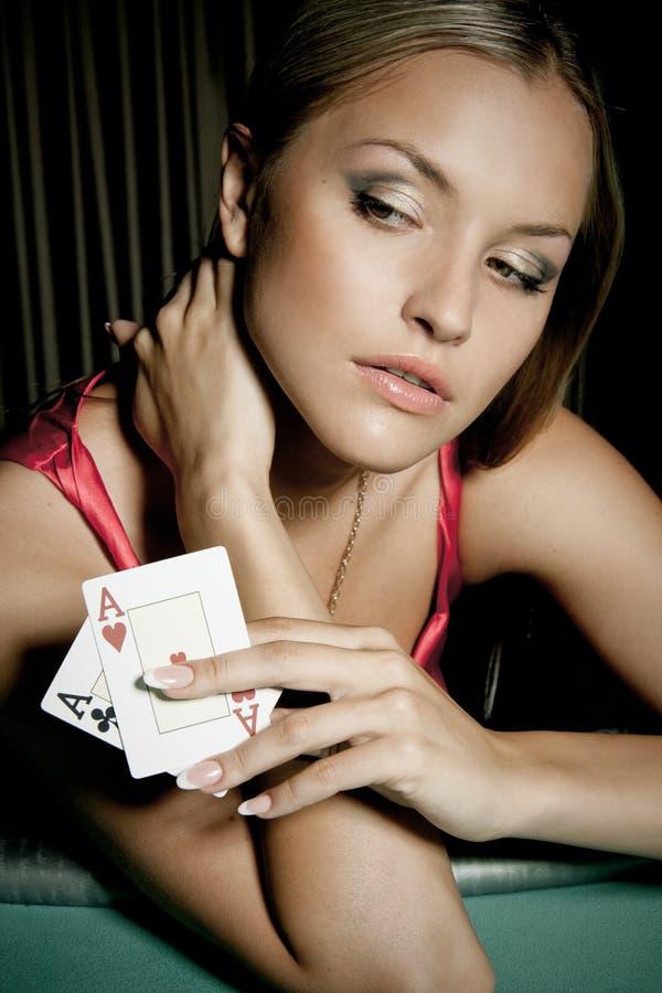 演奏啤牌性感的妇女的娱乐场 免版税库存照片