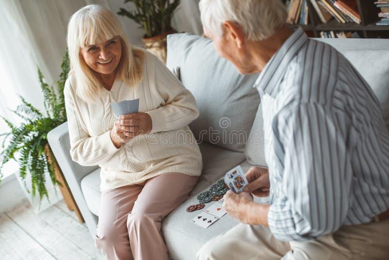 演奏啤牌狡猾的咧嘴的资深在家一起夫妇退休概念 免版税图库摄影