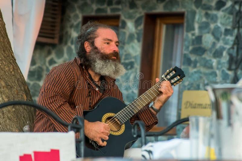 演奏在一把声学吉他的街道音乐家音乐 免版税库存图片